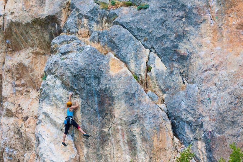 Grimpeur de roche s'attachant à une falaise images libres de droits