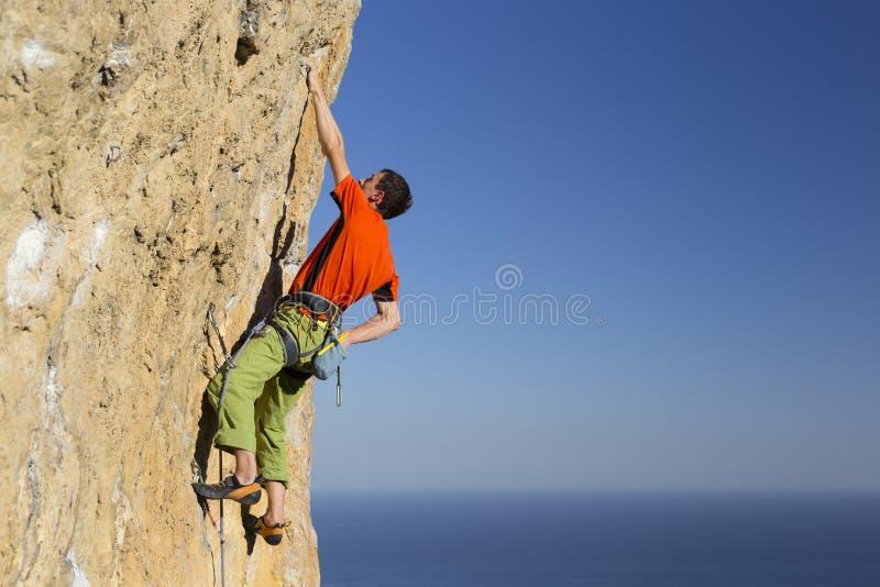 Grimpeur de roche s'attachant à une falaise photos stock