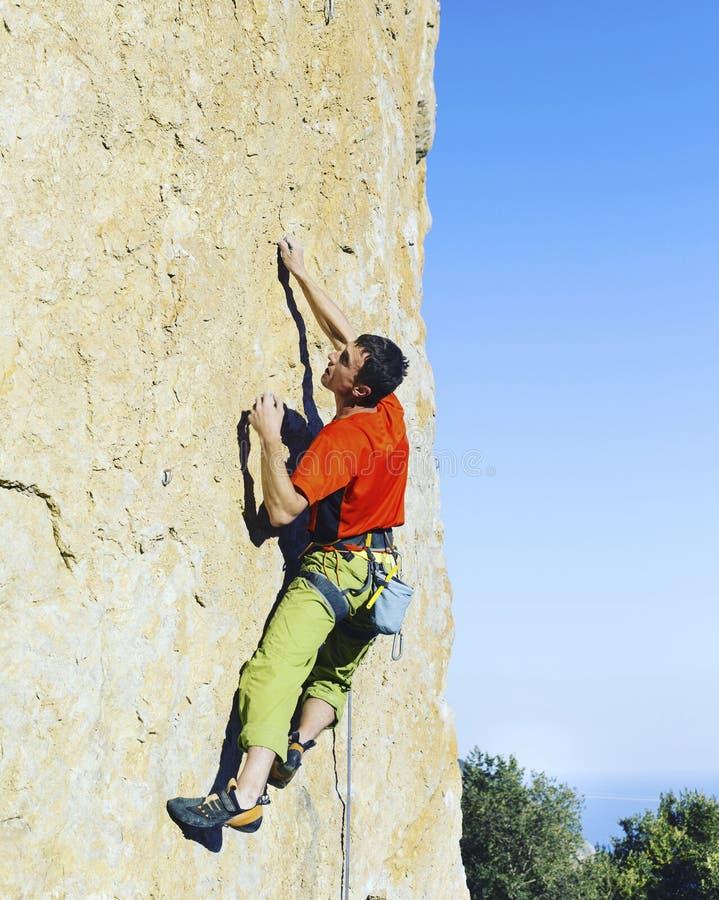 Grimpeur de roche s'attachant à une falaise photo stock