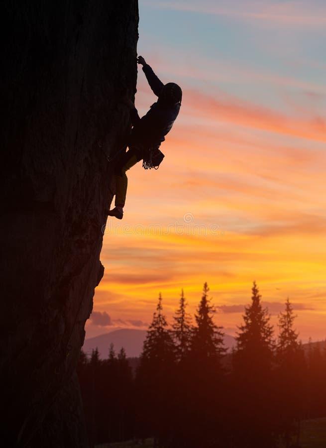 Grimpeur de silhouette s'élevant à la tombée de la nuit, atteignant pour la prochaine main de prise Ciel nuageux orange de couche images libres de droits