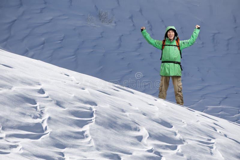 Grimpeur de touristes masculin avec des bras levés sur le fond du paysage neigeux de montagne Geste de réussite image stock
