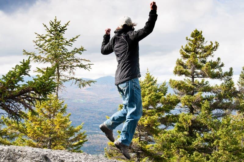 Grimpeur enthousiaste sautant en haut d'une montagne image libre de droits