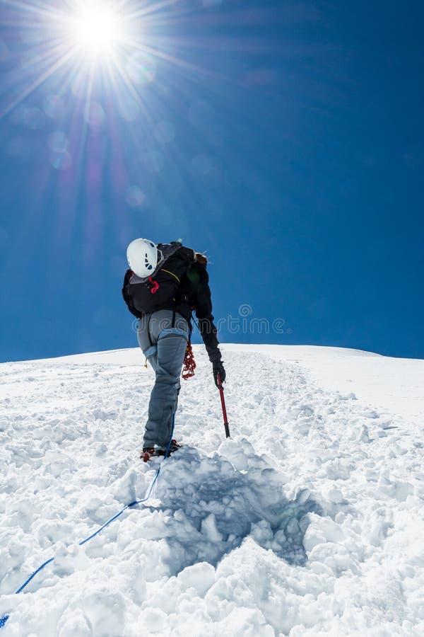 Grimpeur féminin montant une pente neigeuse photo stock