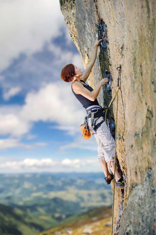 Grimpeur féminin s'élevant avec la corde sur un mur rocheux photographie stock