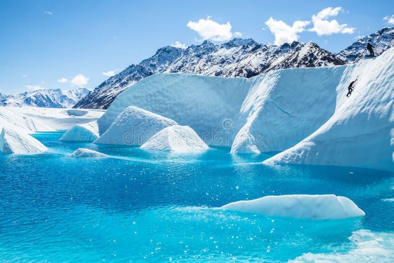 Grimpeur montant un grand mur de glace au-dessus d'un lac glaciaire bleu sur le glacier de Matanuska photos libres de droits