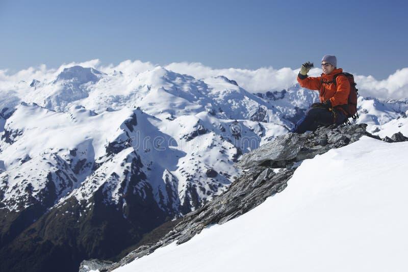 Grimpeur prenant la photo des montagnes de Milou image stock