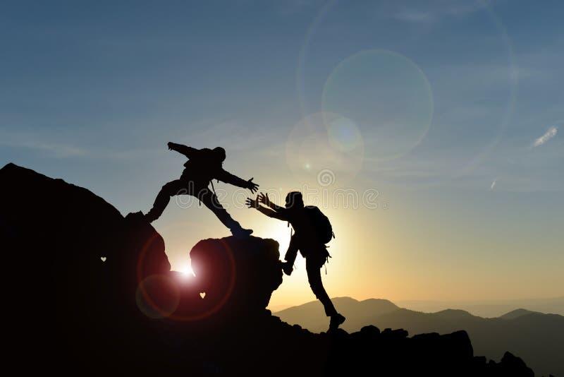 Grimpeurs atteignant le sommet au coucher du soleil photographie stock libre de droits