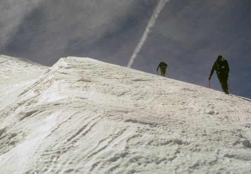 Grimpeurs sur la neige escarpée photos libres de droits
