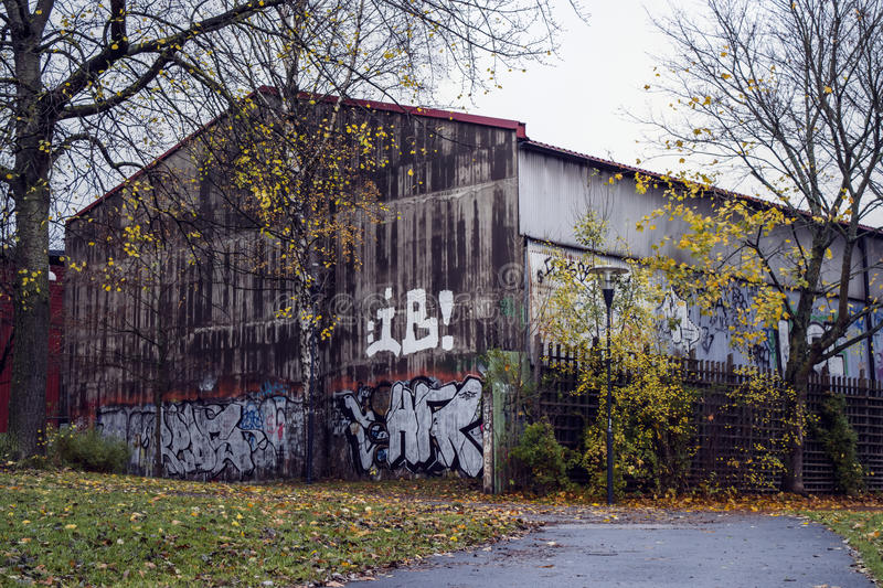 Grimy old house by autumn. An old, worn building with grafitti in an autumn landscape royalty free stock photography