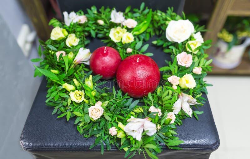 Grinalda bonita das flores em um feriado fêmea o 8 de março Velas vermelhas esféricas no centro da grinalda imagem de stock royalty free