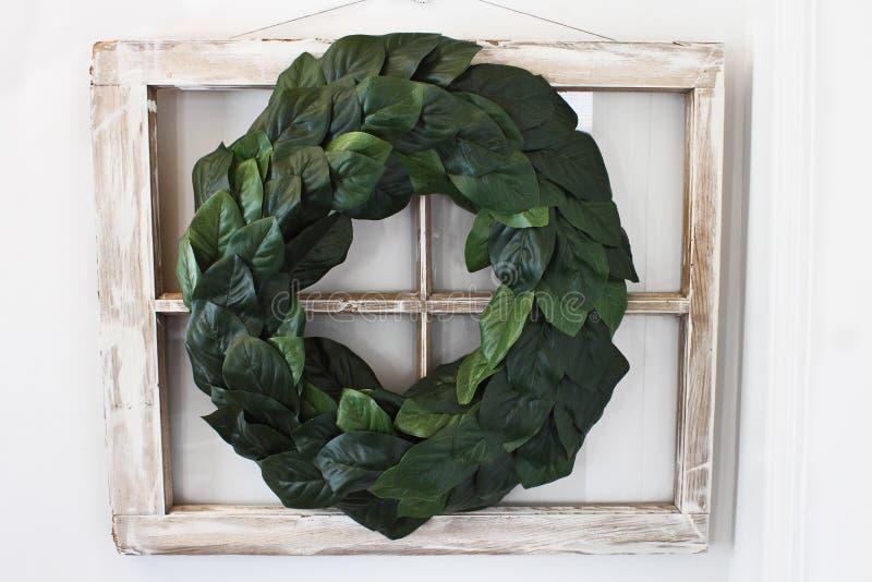 Grinalda da folha da magnólia sobre a janela velha foto de stock royalty free