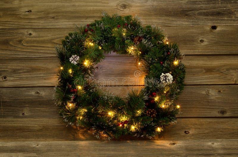 Grinalda do Natal com luzes brancas em placas de madeira rústicas imagem de stock royalty free