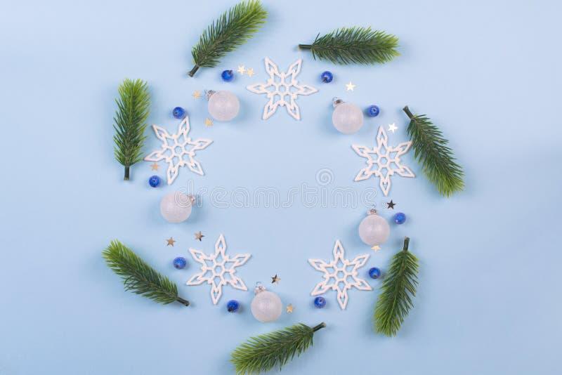 Grinalda do Natal com ramos e flocos de neve do abeto no fundo azul pastel Ornamento com grinalda imagem de stock