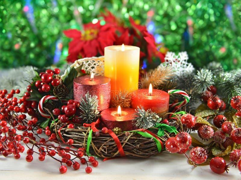 Grinalda do Natal com velas, as coníferas e as bagas ardentes fotografia de stock