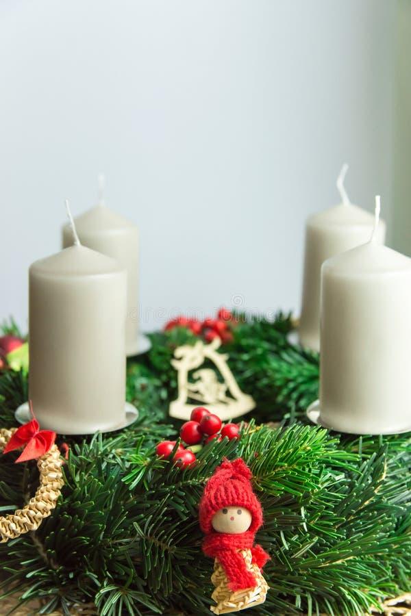 A grinalda do Natal dos ramos de árvore verdes frescos do abeto decorados com anjo de madeira do ornamento vermelho da baga do az imagens de stock