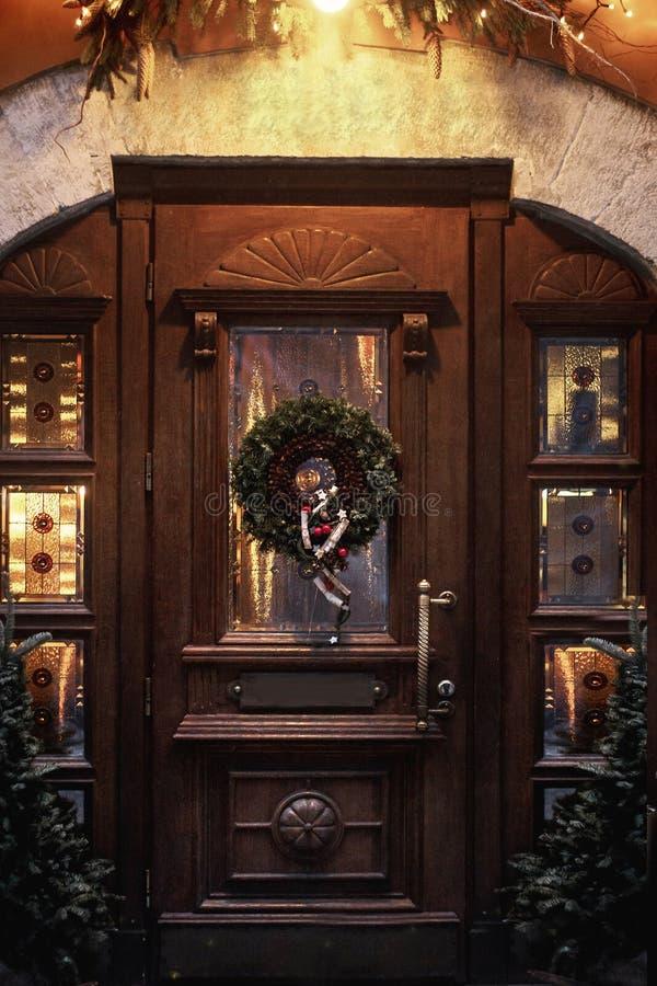 Grinalda do Natal na porta de madeira wi decorados luxo da parte dianteira da loja foto de stock royalty free