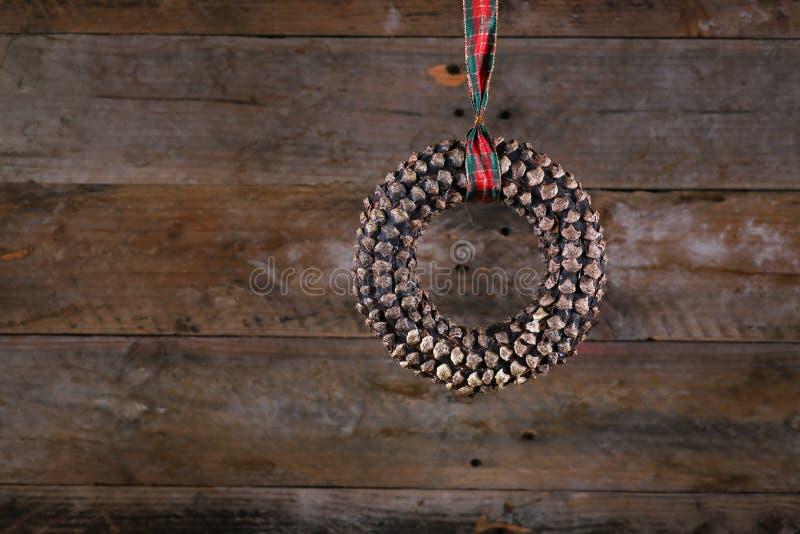 Grinalda e fita do Natal do cone do pinho da forma redonda em rústico velho imagens de stock