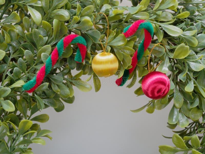 Grinalda ou festão artificial do Natal feita pela folha plástica decorada pelo bastão vermelho e branco e pela maçã vermelha e am imagem de stock royalty free