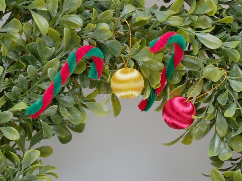Grinalda ou festão artificial do Natal feita pela folha plástica decorada pelo bastão vermelho e branco e pela maçã vermelha e am foto de stock