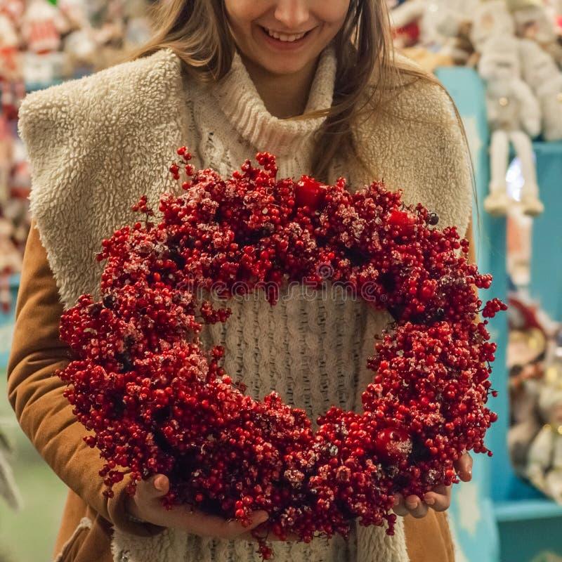 Grinalda rústica do Natal que guarda bagas vermelhas nos ramos na loja Imagem temperamental atmosférica na oficina do feriado imagens de stock royalty free