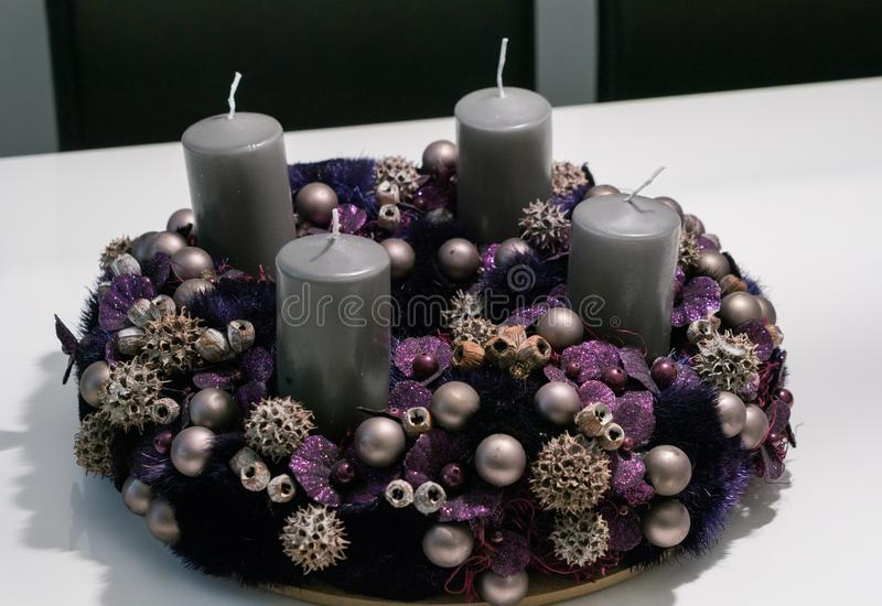 Grinalda roxa do advento com quinquilharias e quatro velas cinzentas em uma tabela branca fotografia de stock royalty free