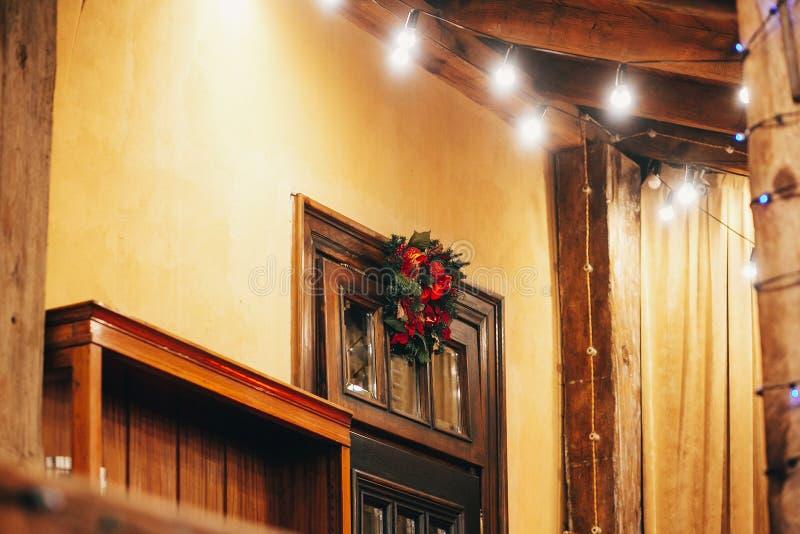 A grinalda tradicional do Natal com os ornamento vermelhos em de madeira velho faz imagens de stock