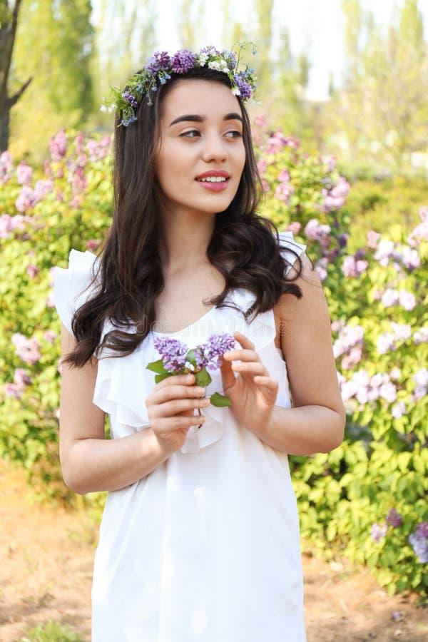 Grinalda vestindo da flor da jovem mulher bonita perto do arbusto de florescência no dia de mola ensolarado imagens de stock royalty free