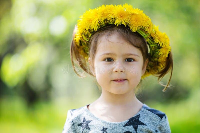 Grinalda vestindo da menina bonito dos dentes-de-leão fora foto de stock