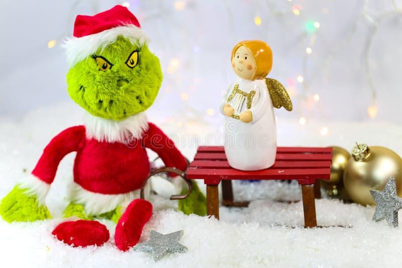Grinch με έναν άγγελο, bokeh, άσπρο υπόβαθρο στοκ φωτογραφίες