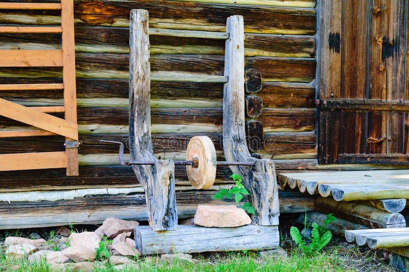 Grind stone. Circular grindstone with crank on some serious wooden stand leaning against a timbered farm building. Part of door and stairway on the right. Part royalty free stock photos