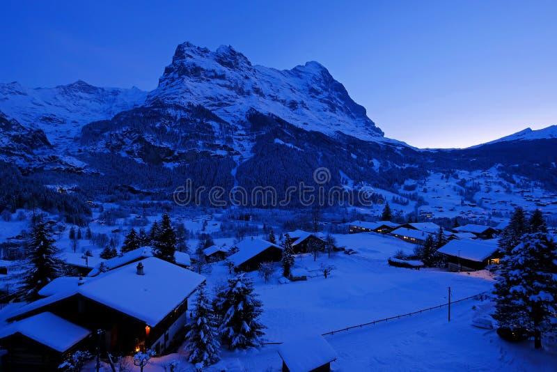 Grindelwalddorp bij schemer met MT De Eigerpiek op de achtergrond, sneeuw behandelde landschap in de winter, Zwitserland royalty-vrije stock afbeeldingen