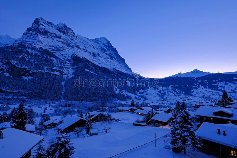 Grindelwalddorp bij schemer met MT De Eigerpiek op de achtergrond, sneeuw behandelde landschap in de winter, Zwitserland stock foto's