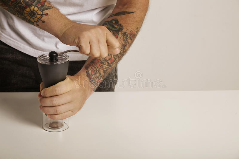 Grinding coffee with a manual grinder royalty free stock image