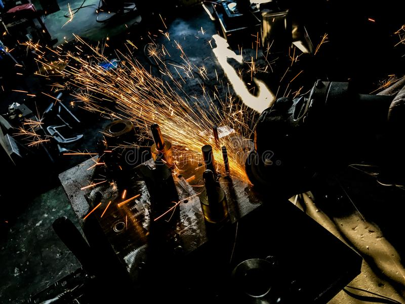 Welding and grinding within the manufacturing process Sparks and smoke. royalty free stock photo