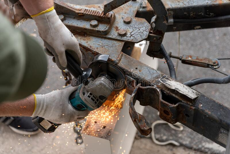 Grinding off a piece of metal from a hitch stock image