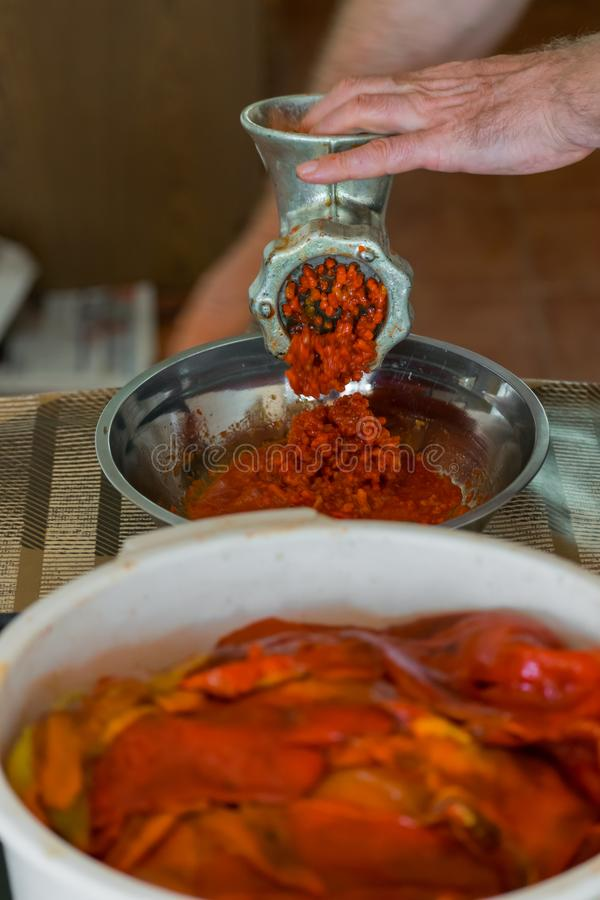 Grinding paprika for Ajvar. A white Caucasian man is grinding paprika for delicious traditional Serbian meal called Ajvar royalty free stock photos