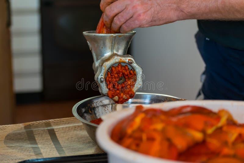 Grinding paprika for Ajvar. A white Caucasian man is grinding paprika for delicious traditional Serbian meal called Ajvar stock photo