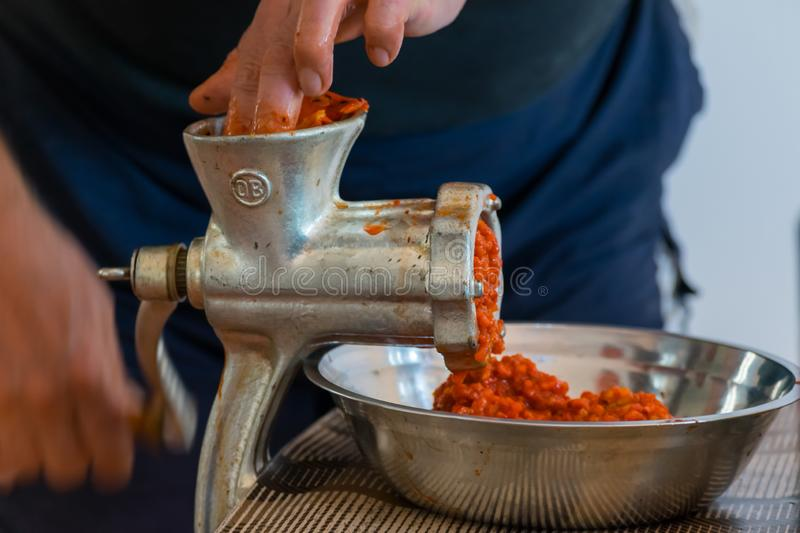 Grinding paprika for Ajvar. A white Caucasian man is grinding paprika for delicious traditional Serbian meal called Ajvar royalty free stock photography