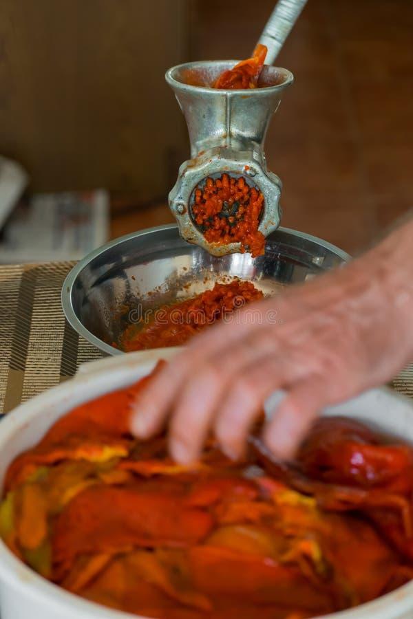 Grinding paprika for Ajvar. A white Caucasian man is grinding paprika for delicious traditional Serbian meal called Ajvar stock images