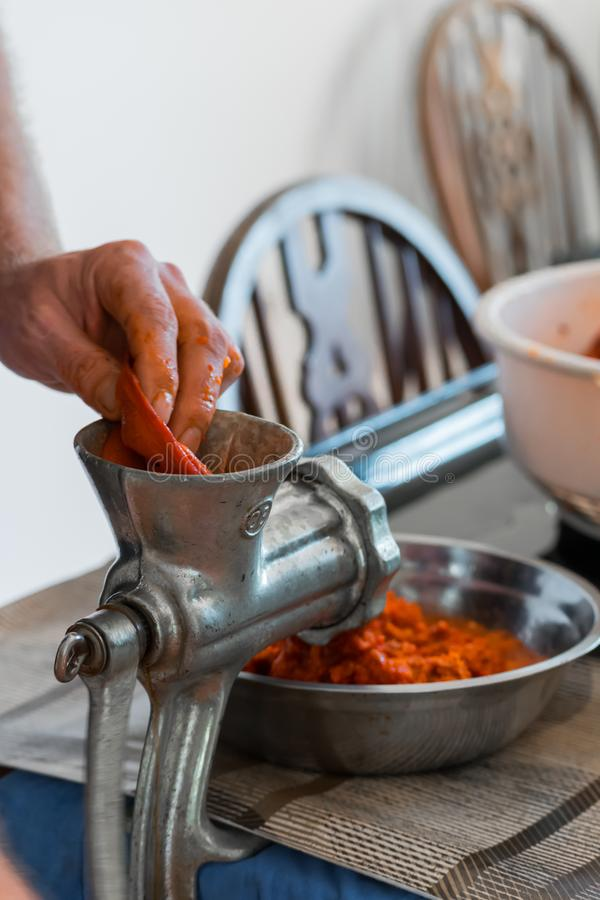 Grinding paprika for Ajvar. A white Caucasian man is grinding paprika for delicious traditional Serbian meal called Ajvar royalty free stock images