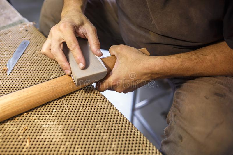 Grinding and polishing the guitar wooden neck. hand-made musical instruments royalty free stock photos