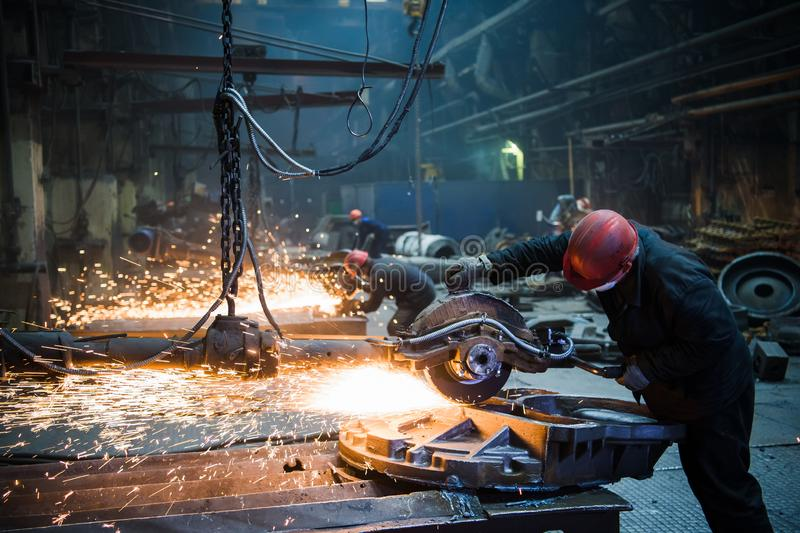 Grinding in a steel factory. Worker with a big saw cutting metal. royalty free stock image