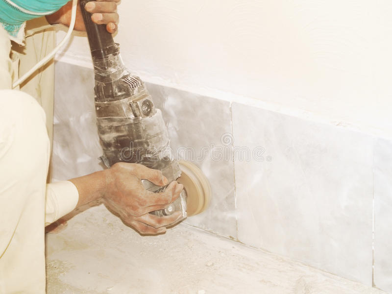 Grinding The Tiled Floor. Construction worker grinding the tiled floor stock image