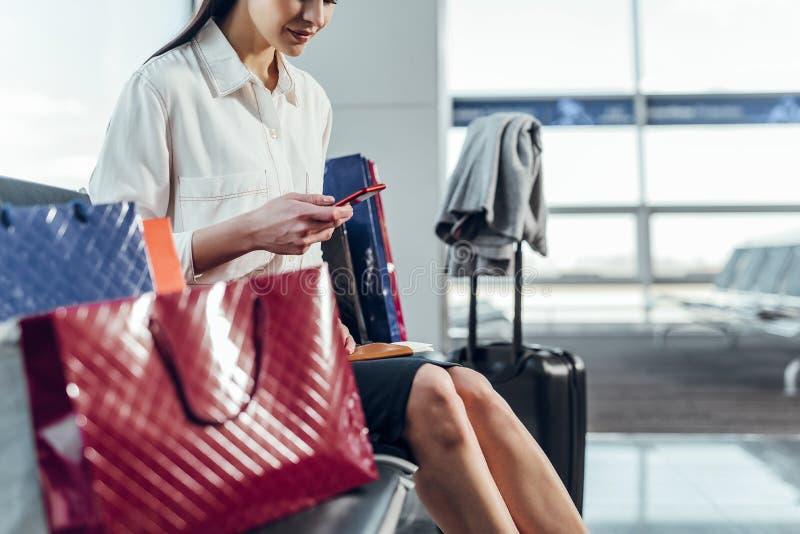 Grinning женщина послание пока ждущ самолет стоковые изображения rf