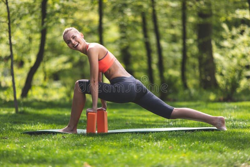 Grinning женщина тренировать с блоками йоги outdoors стоковое фото rf
