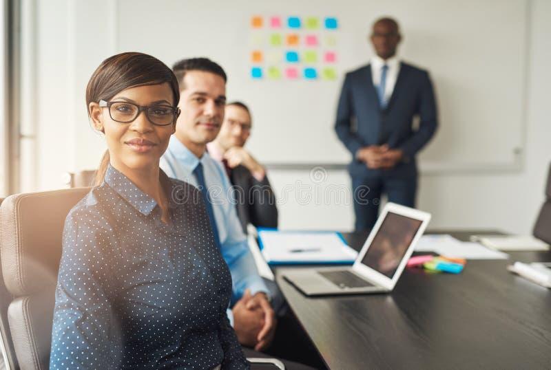 Grinning женщина усаженная с коллегами в встрече стоковые фото
