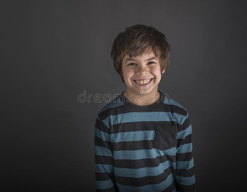 Grinning boy in striped shirt stock photo