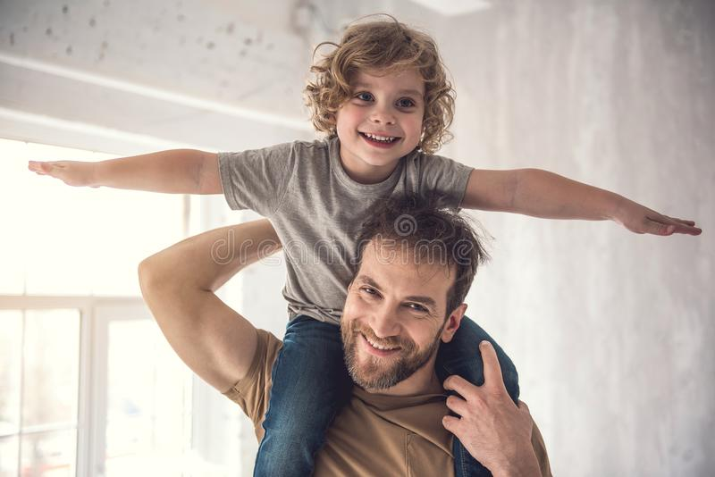 Grinning father is carefully raising son on shoulders stock photo