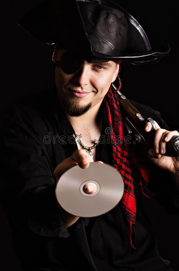 Grinning pirate with a CD-ROM. Photo of a smiling man in a pirate costume holding out compact disc royalty free stock photos