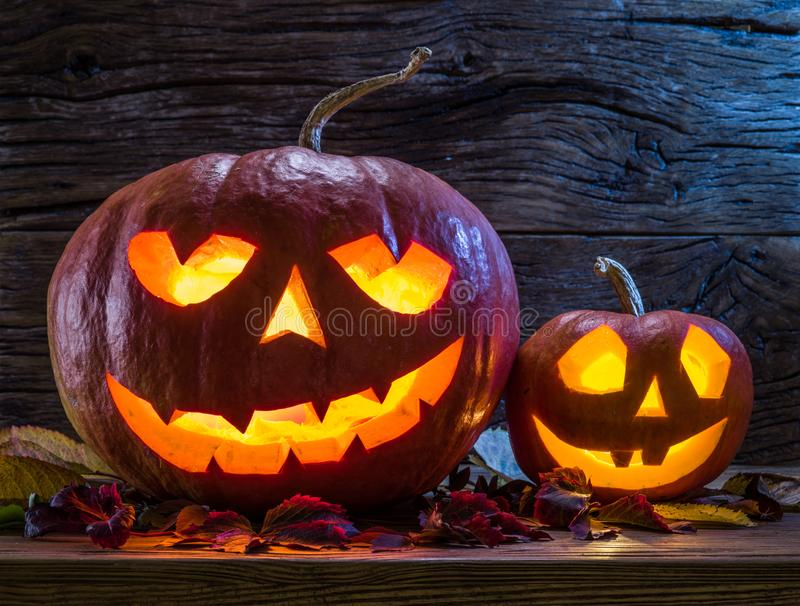 Grinning pumpkin lantern or jack-o`-lantern is one of the symbols of Halloween. Halloween attribute. Wooden background.  stock image